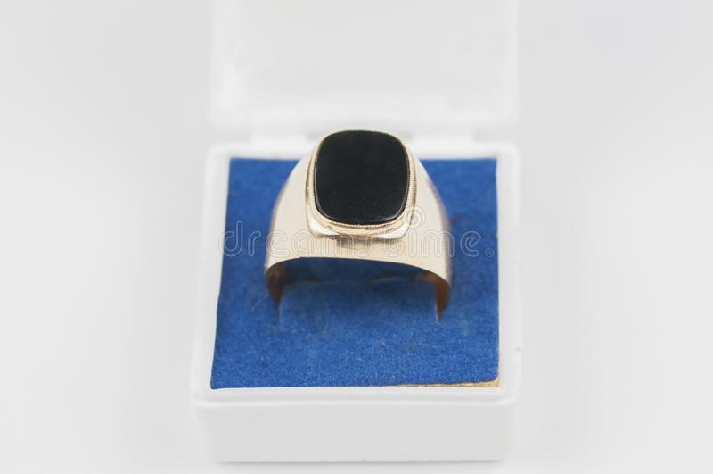 Anneau d'or masculin avec la pierre noire dans une boîte sur un fond blanc image stock