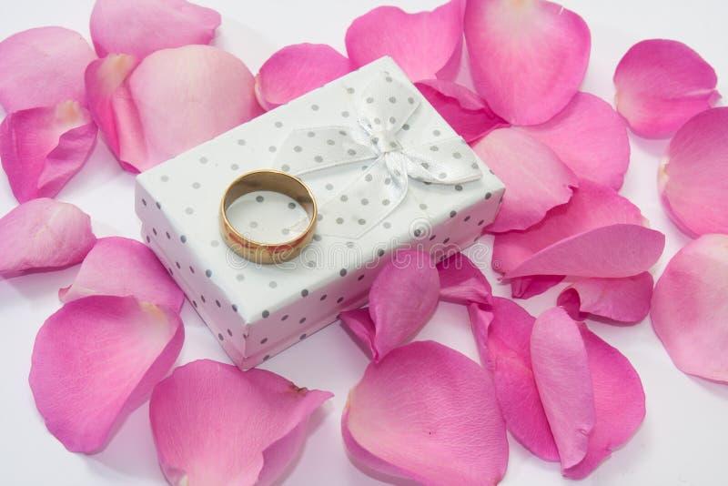 Anneau d'or sur le boîte-cadeau blanc et les pétales de rose roses photo libre de droits
