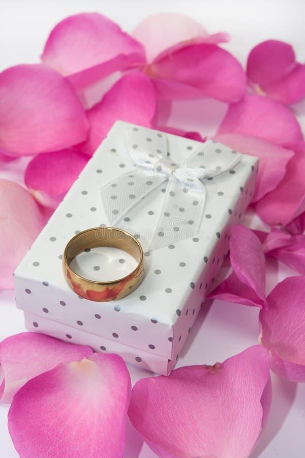Anneau d'or sur le boîte-cadeau blanc et les pétales de rose roses image stock