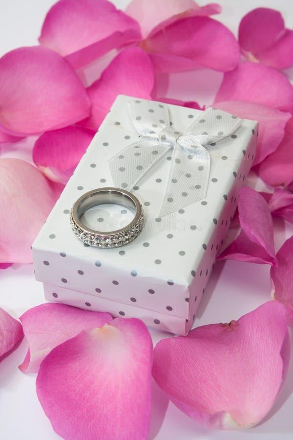 Anneau d'or sur le boîte-cadeau blanc et les pétales de rose roses photos stock