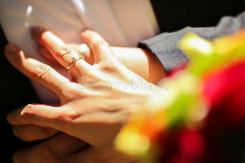 Anneau de jeune mariée tenant les mains et la fleur photographie stock libre de droits