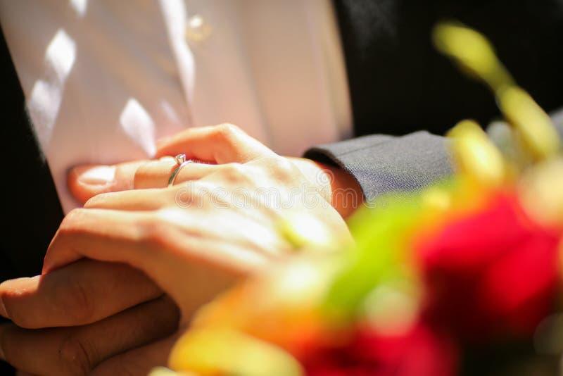 Anneau de jeune mariée tenant les mains et la fleur photographie stock