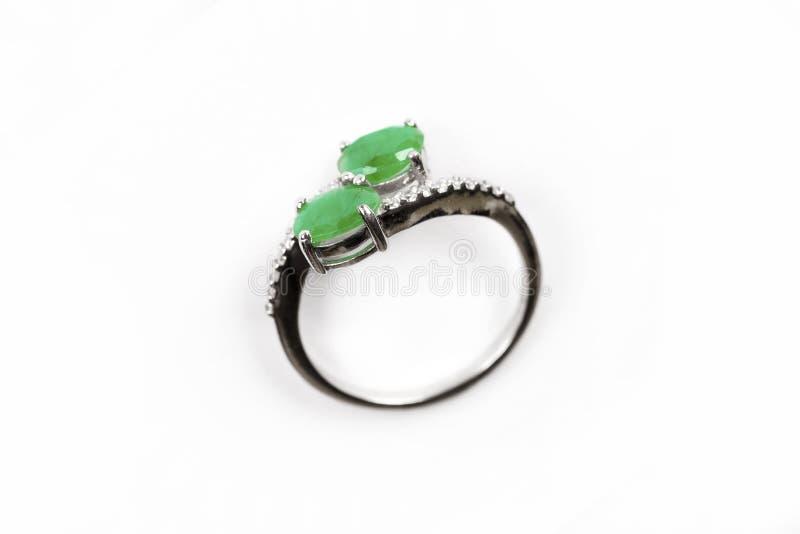 Anneau de luxe avec la gemme verte d'isolement sur le fond blanc images stock