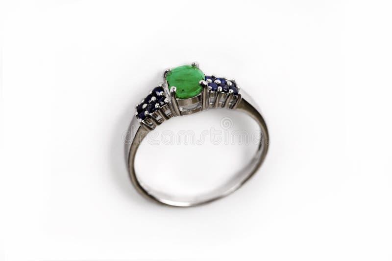 Anneau de luxe avec la gemme verte d'isolement sur le fond blanc photographie stock libre de droits
