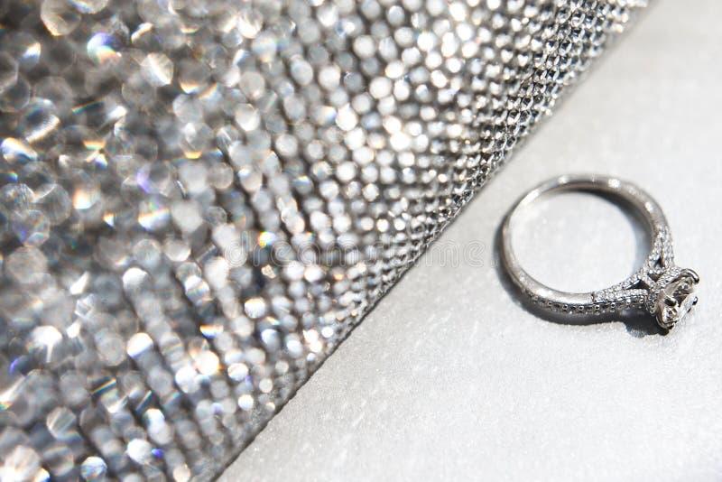 Anneau de mariage avec le sac à main argenté sur la table blanche images stock