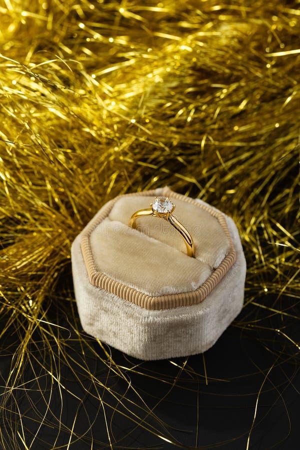 Anneau de mariage d'or avec le diamant dans la boîte d'anneau de velours de cru dans les décorations d'or de Noël photos libres de droits
