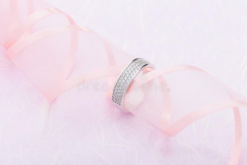 Anneau de mariage d'or blanc avec des diamants sur le fond rose avec le ruban images stock
