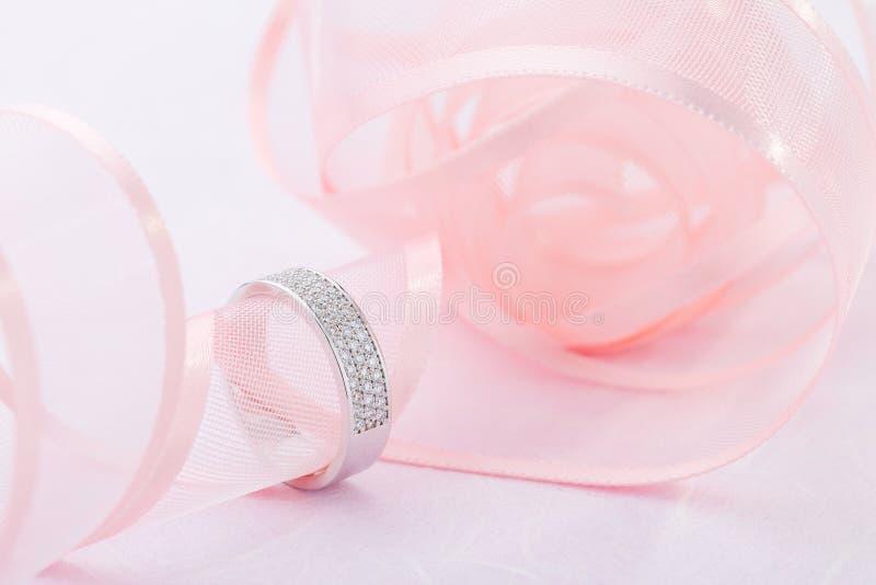 Anneau de mariage d'or blanc avec des diamants sur le fond rose avec le ruban photos libres de droits