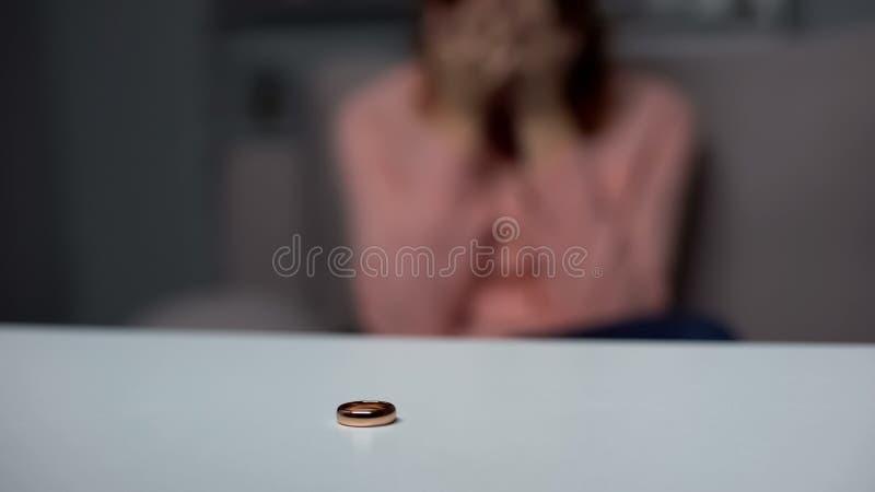 Anneau de mariage sur la table, femme pleurante sur le fond, dissolution de couples, divorce photos libres de droits