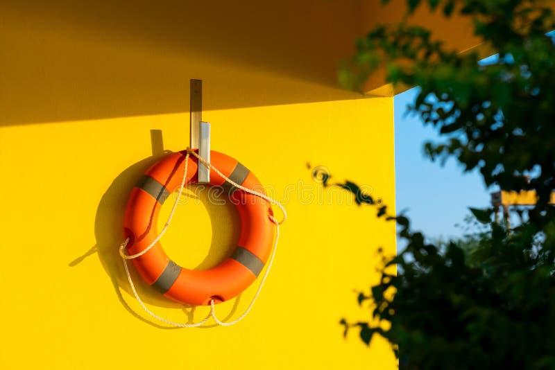 Anneau de vie orange lumineux accroché contre sur le mur en béton jaune lumineux photographie stock libre de droits