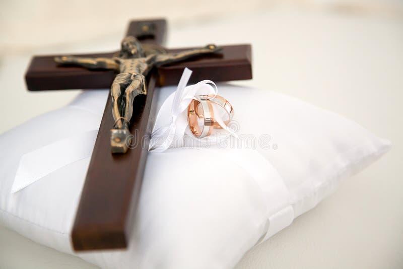 Anneaux chrétiens de croix et de mariage sur le coussin blanc photographie stock