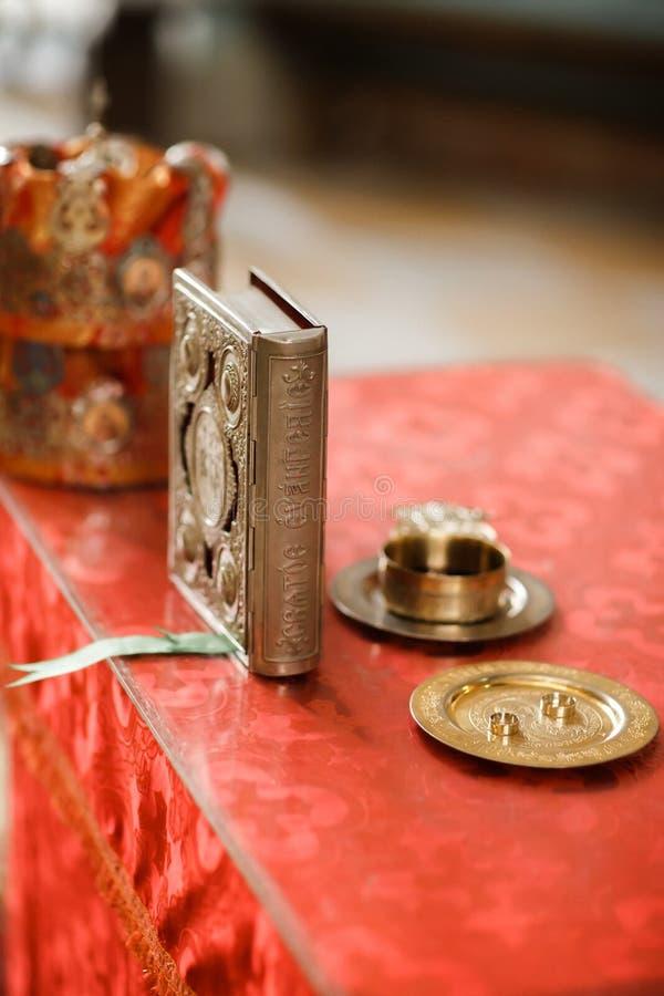 Anneaux, couronnes et bible de mariage à la table avec la croix et au verre de la vigne images stock