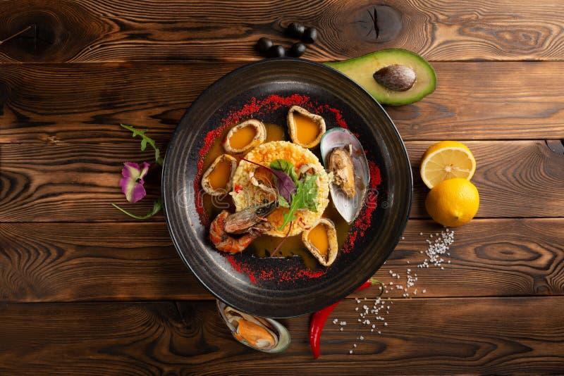 Anneaux cuits au four de calmar avec du riz et des ?pices dans le plat noir photos stock