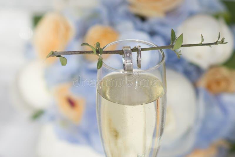 Anneaux de mariage autour de brindille sur le verre photo libre de droits