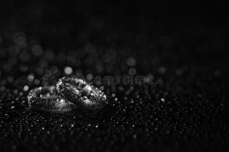 Anneaux de mariage d'or argenté ou blanc sous la pluie photo libre de droits
