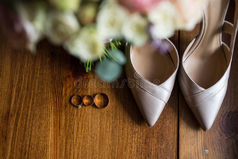 Anneaux de mariage d'or, bagues de fiançailles et chaussures beiges nuptiales sur le fond brun accessoires photographie stock