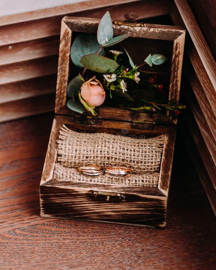Anneaux de mariage d'or dans la belle boîte rustique avec des fleurs intérieur et sur le fond en bois photo libre de droits