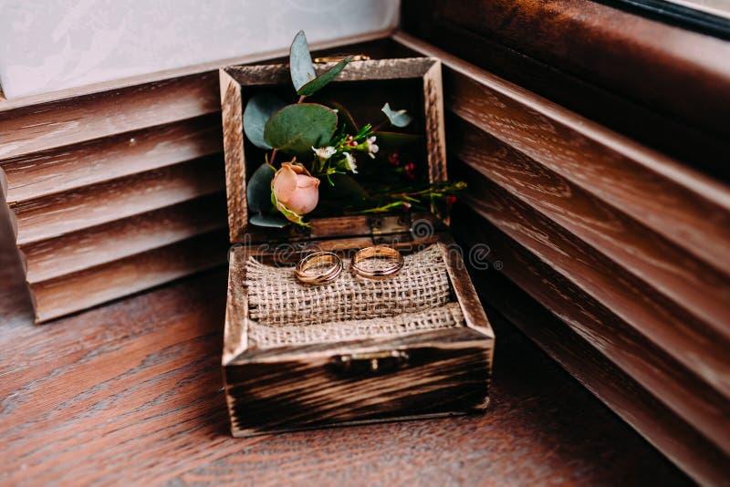 Anneaux de mariage d'or dans la belle boîte rustique avec des fleurs intérieur et sur le fond en bois images libres de droits