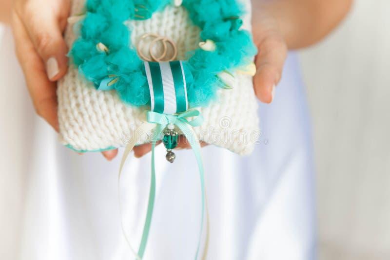 Anneaux de mariage d'or sur le petits bleu et coussin de turquoise image stock