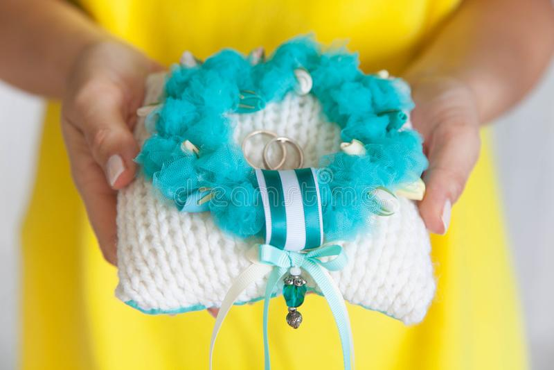 Anneaux de mariage d'or sur le petits bleu et coussin de turquoise photo libre de droits
