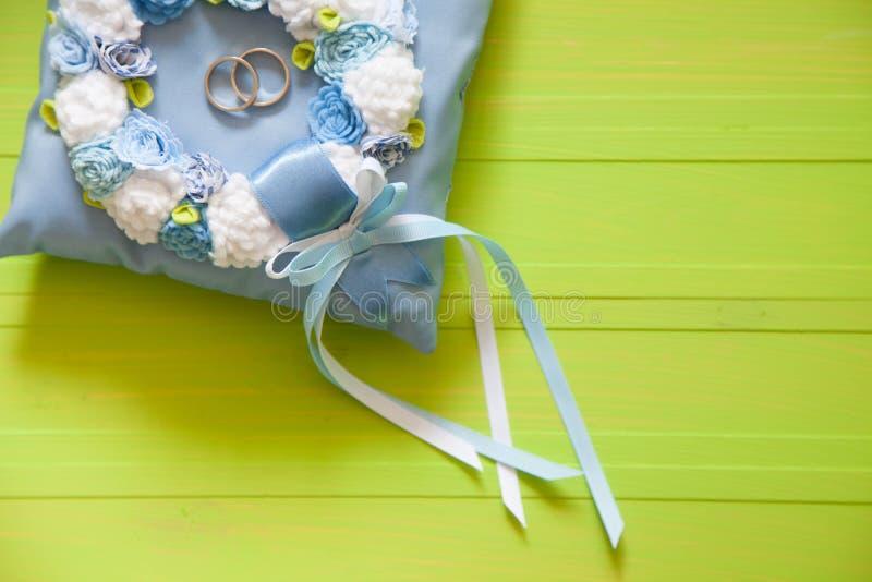 Anneaux de mariage d'or sur le petits bleu et coussin de turquoise Backgr photographie stock