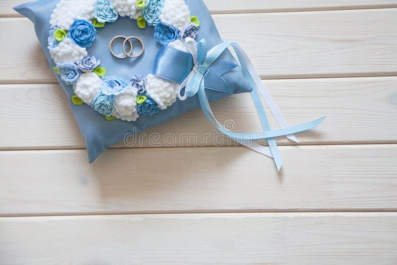 Anneaux de mariage d'or sur le petits bleu et coussin de turquoise Backgr photo stock
