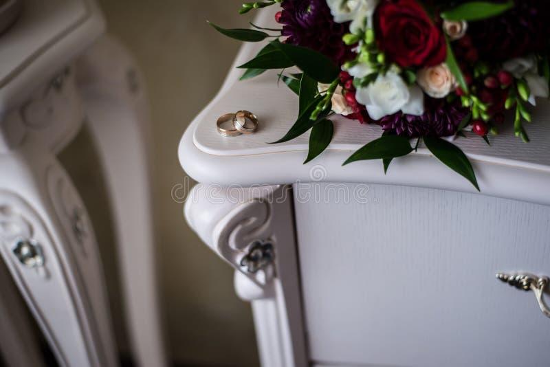 Anneaux de mariage d'or sur une table blanche image libre de droits