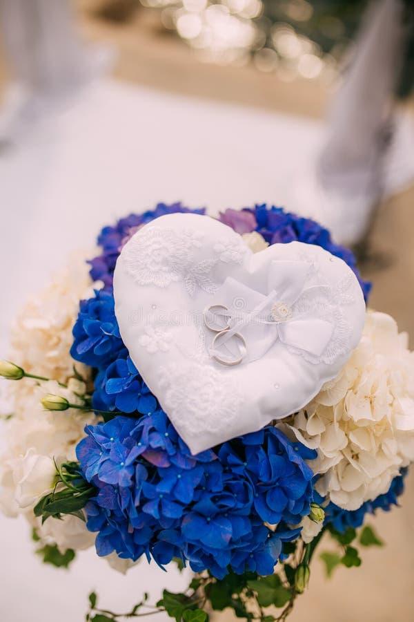 Anneaux de mariage d'un couple nouveau-marié sur un coussin pour des anneaux images libres de droits
