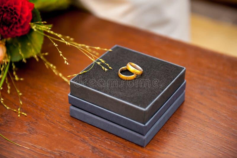 Anneaux de mariage dans la caisse noire sur la table en bois image libre de droits