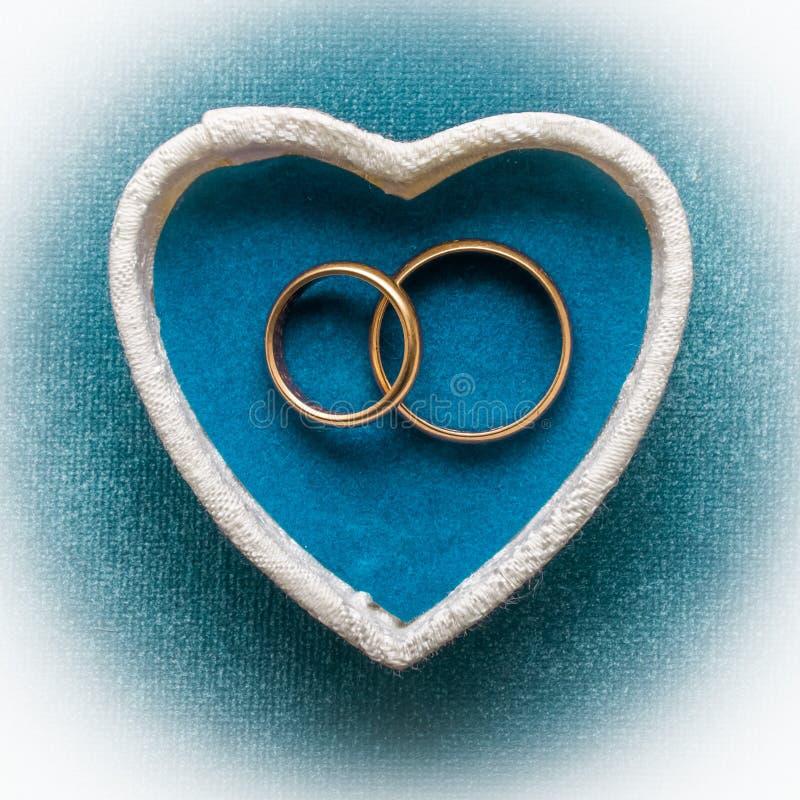 Anneaux de mariage dans le boîtier blanc en forme de coeur photographie stock libre de droits