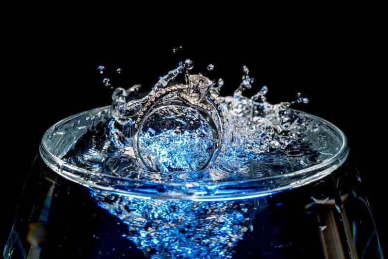 Anneaux de mariage descendant dans un verre d'eau photo libre de droits