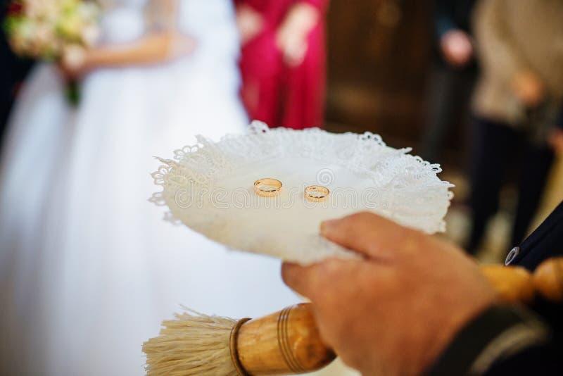 Anneaux de mariage du plat actuel du prêtre à la cérémonie de mariage à images libres de droits