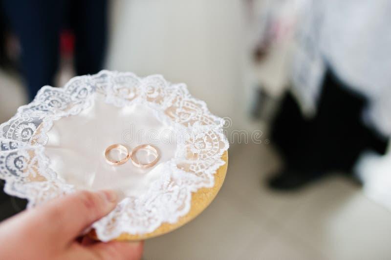 Anneaux de mariage du plat d'or rond actuel du prêtre sur l'église photographie stock