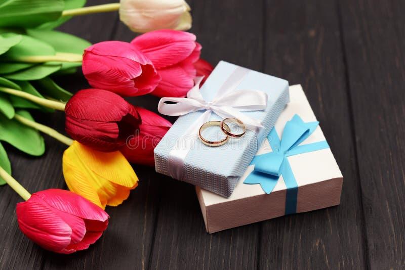 Anneaux de mariage de fête d'or sur des boîte-cadeau avec les fleurs rouges de tulipes images libres de droits
