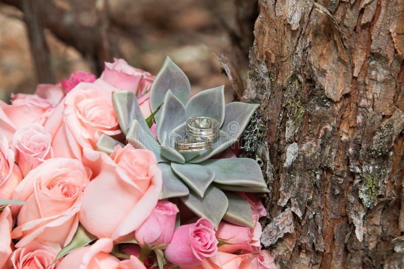 Anneaux de mariage sur la jeune mariée de bouquet images stock