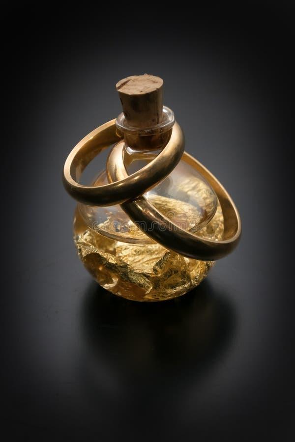 Anneaux de mariage sur la petite bouteille de feuille d'or photos libres de droits
