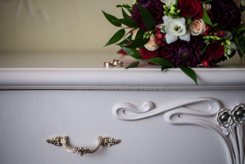 Anneaux de mariage sur la raboteuse antique blanche photo stock