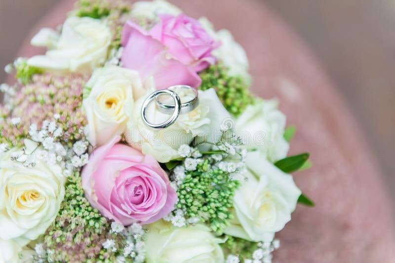 Anneaux de mariage sur le bouquet lumineux de fleur photographie stock libre de droits