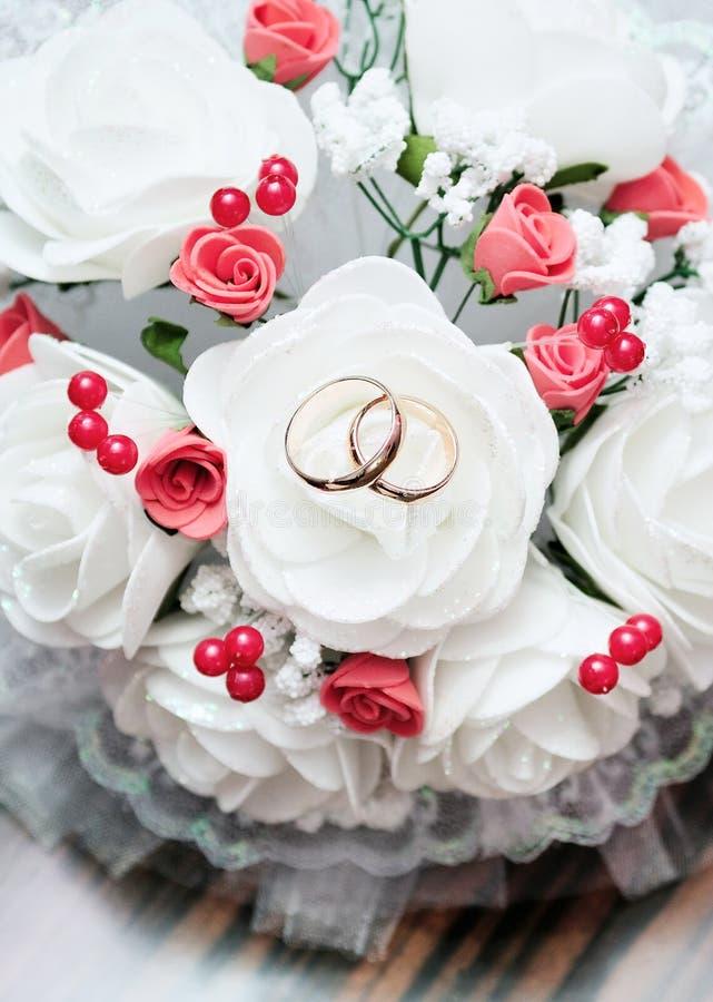 Anneaux de mariage sur le bouquet nuptiale photo stock