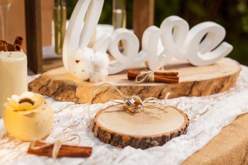 Anneaux de mariage sur le tronçon en bois photo stock