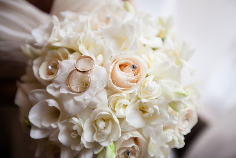 Anneaux de mariage sur un bouquet des fleurs image libre de droits