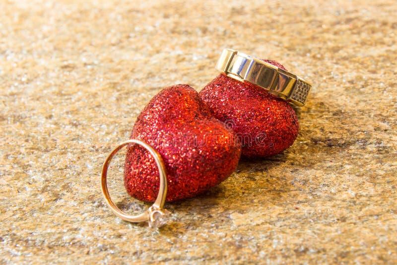 Anneaux de mariage sur une pierre naturelle avec des inclusions d'or indigène Mains et coeurs d'offre photo libre de droits