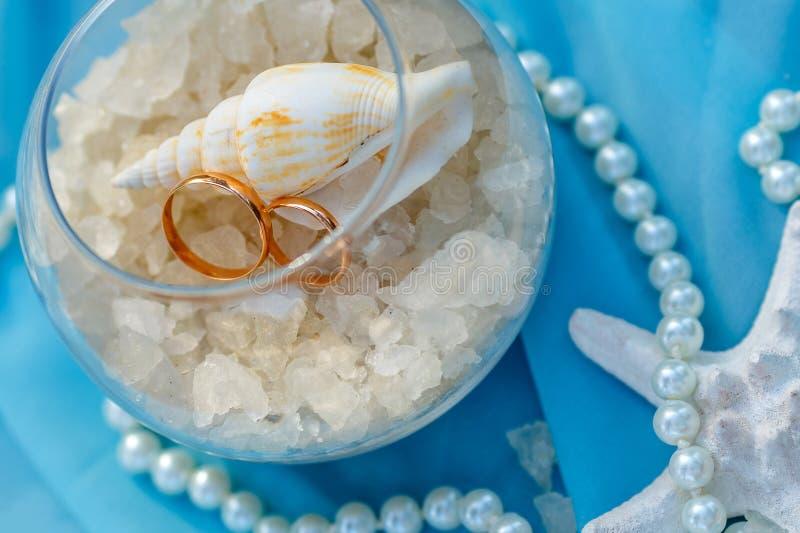 Anneaux de mariage, thème nautique, étoiles de mer et perle photographie stock