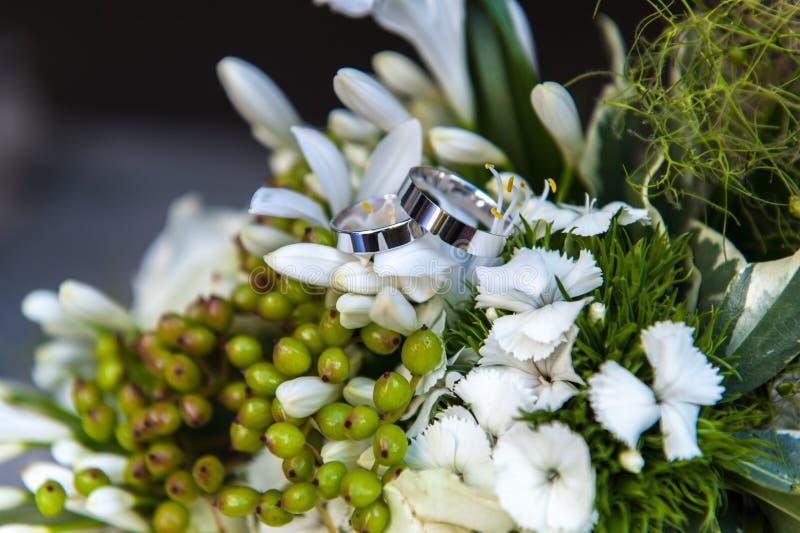 Anneaux de mariages sur le bouquet de fleur photographie stock libre de droits