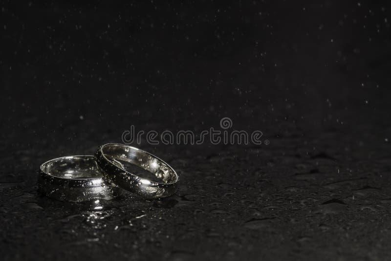 Anneaux de noces d'argent sur un fond de roche avec les gouttelettes et le jet d'eau photographie stock