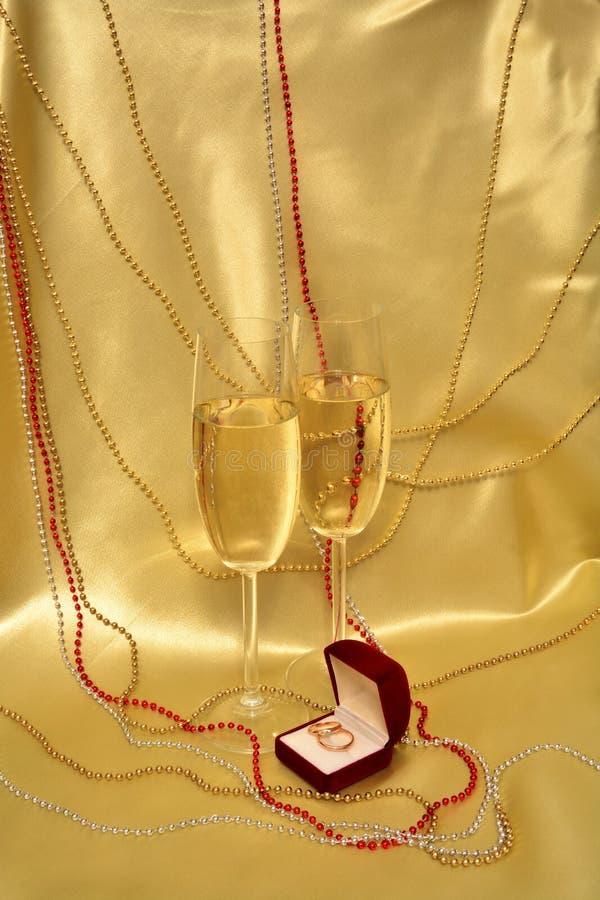 Anneaux et verres de mariage avec le vin mousseux sur un fond d'or photographie stock libre de droits