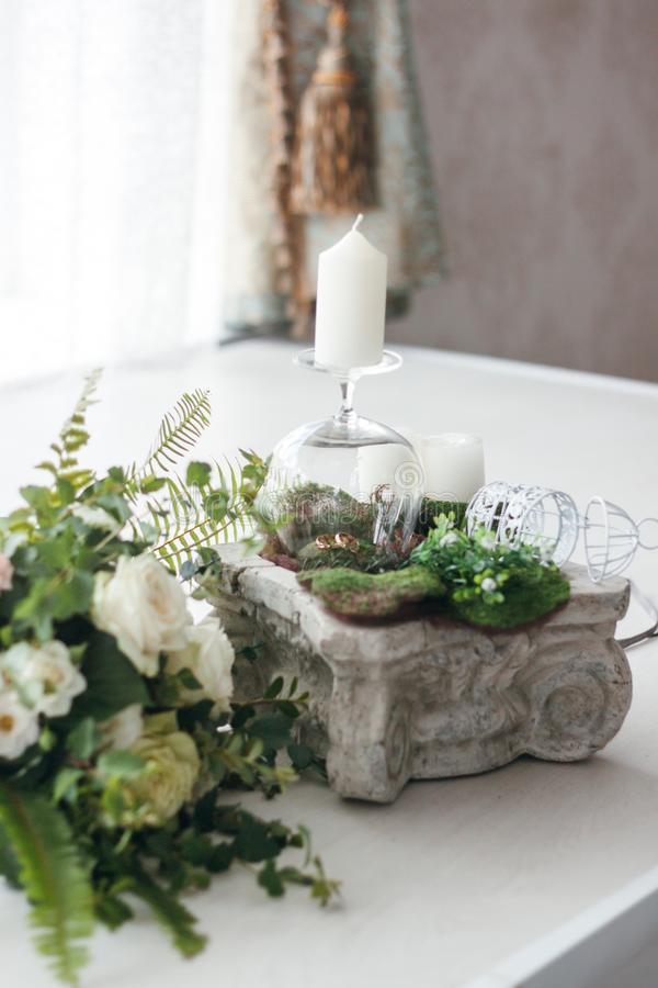 Anneaux les épousant, bougies, un verre, une cage décorative sur le chapiter, un bouquet des roses blanches image stock