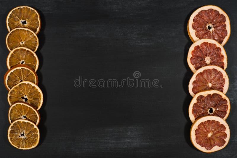Anneaux secs d'orange et de pamplemousse sur un tableau noir photo stock