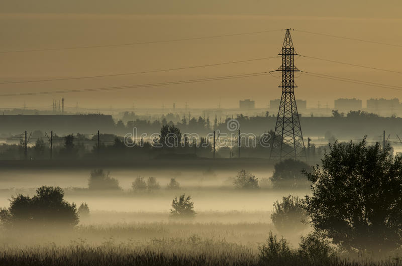 Annebbi sopra i campi e la torre delle linee elettriche sulle periferie della città immagine stock libera da diritti