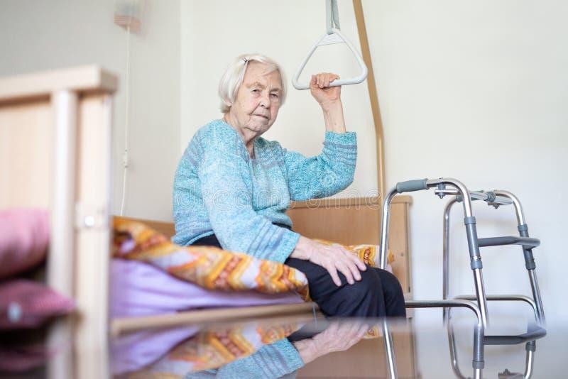 96 anni anziani della donna che si siede sul letto medico in hospic fotografia stock libera da diritti